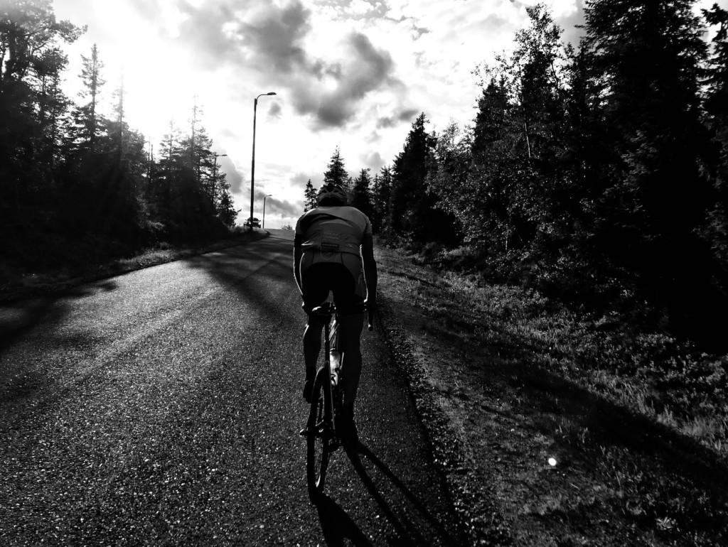 Pyöräilijä ajaa Iso-Syötteellä maantiellä selkä kameraan päin. Kuva on mustavalkoinen.